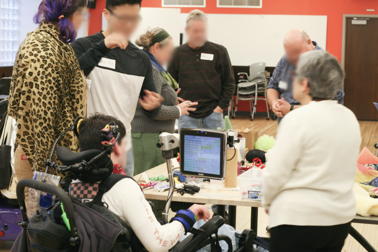 A photograph taken at a workshop with a person using an AAC device, her close conversational partner, and puppeteers. All participants stand around a table full of craft supplies and are engaged in coversation.